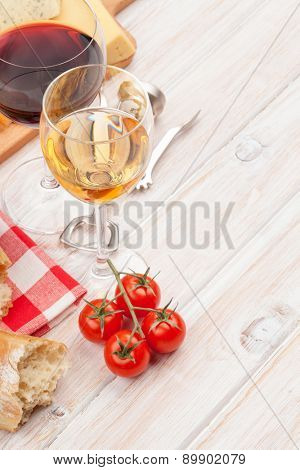 White and red wine, cheese and bread on white wooden table background. Top view with copy space