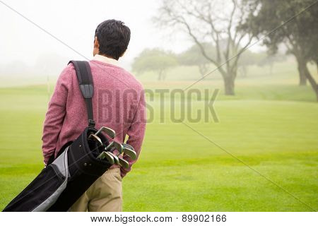 Golfer walking and holding his golf bags in golf course