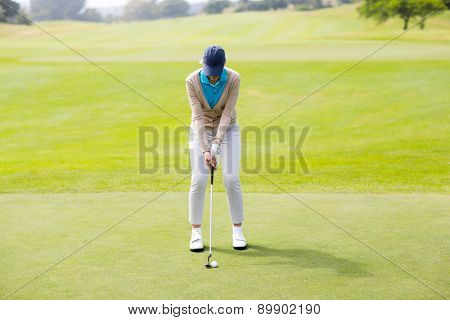 Female golfer putting her ball on a sunny day at the golf course