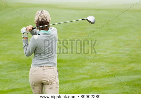 Lady golfer teeing off for the day on a foggy day at the golf course