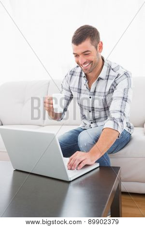 Smiling man with a mug using a laptop sitting on a sofa at home