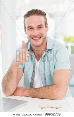 Positive businessman at desk with thumb up in his office
