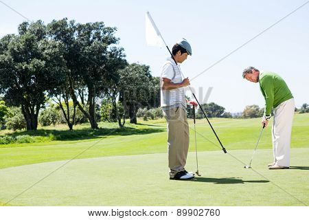 Golfer holding hole flag for friend putting ball at the golf course