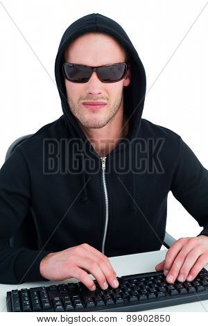 Stern hacker with sunglasses typing on keyboard on white background