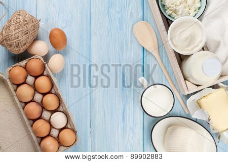 Dairy products on wooden table. Sour cream, milk, cheese, egg, yogurt and butter. Top view with copy space