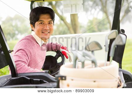 Happy golfer driving his golf buggy smiling at camera at the golf course
