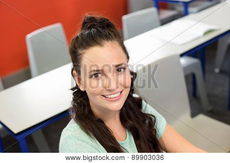 Portrait of smiling female student sitting in the classroom