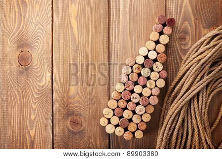 Wine bottle shaped corks over rustic wooden table background. View from above with copy space