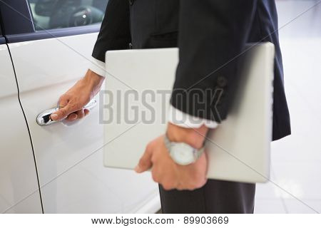 Man holding a car door handles with a laptop at new car showroom