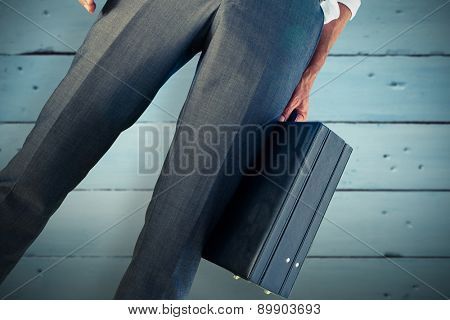 Businessman holding briefcase against painted blue wooden planks
