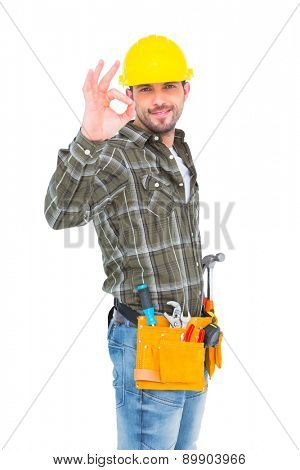 Portrait of smiling handyman gesturing okay on white background