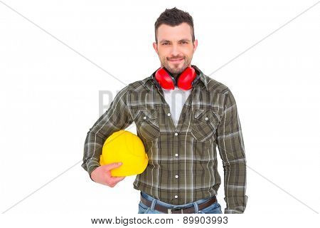 Handyman with earmuffs holding helmet on white background