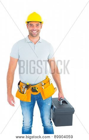 Portrait of smiling handyman holding toolbox on white background