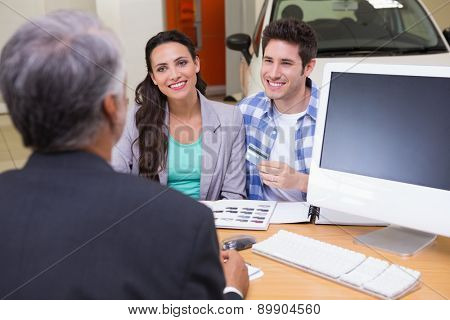 Smiling couple holding credit card to buy a car at new car showroom