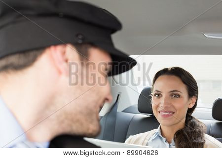Young businesswoman being chauffeured while working in the car