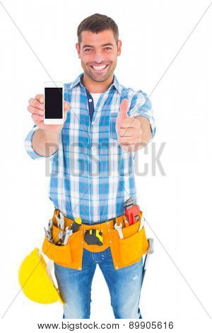 Portrait of happy repairman showing mobile phone white gesturing thumbs up on white background