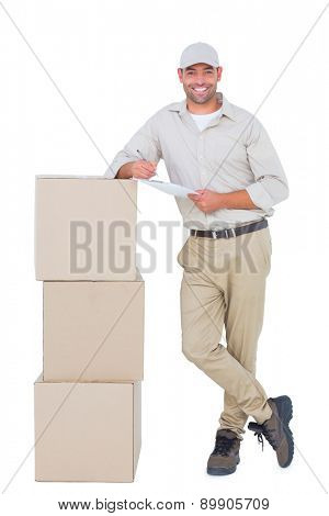 Full length portrait of confident delivery man with clipboard leaning on cardboard boxes on white background