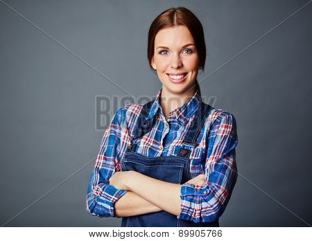 Pretty young woman in coveralls looking at camera with smile