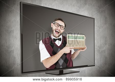 Geeky hipster holding a retro radio against dark background