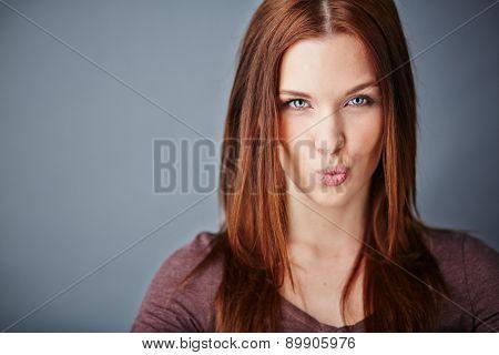 Young woman expressing air kiss while looking at camera