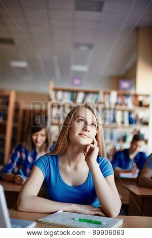 Cute girl daydreaming at lesson in college