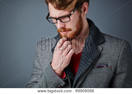 Pensive young man in smart casualwear and eyeglasses