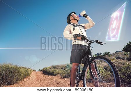 Fit cyclist drinking water on country terrain against fitness interface
