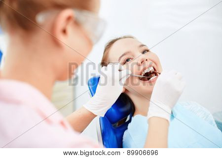 Young female sitting at the dentist and having checkup