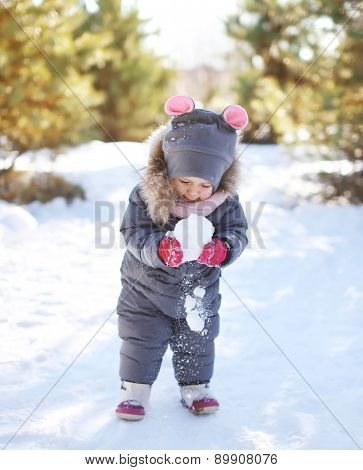 Child Playing With Snow In Sunny Winter Day