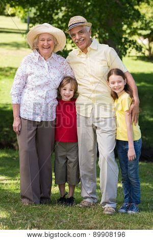 Happy grandparents with their grandchildren at the garden on a sunny day