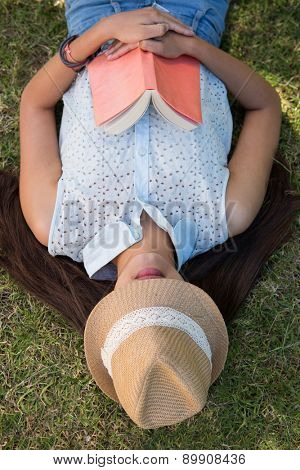 Brunette napping in the park with book on a summers day