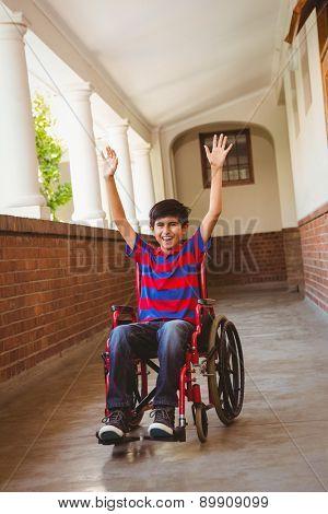 Portrait of cute little boy in wheelchair in school corridor