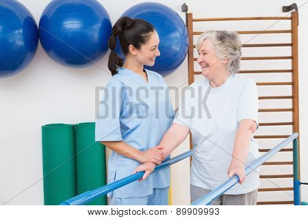 Senior woman walking with parallel bars with therapist in fitness studio