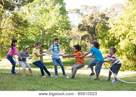 Children having a tug of war in park on a sunny day