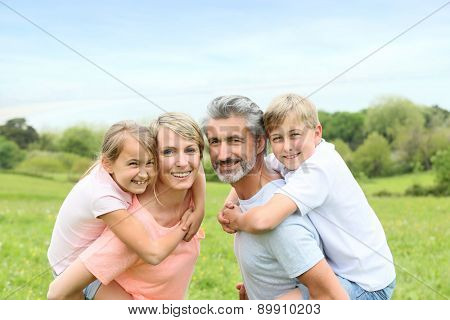 Parents giving piggyback ride to kids in countryside