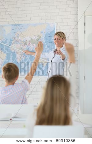 Teacher in classroom teaching geography to pupils