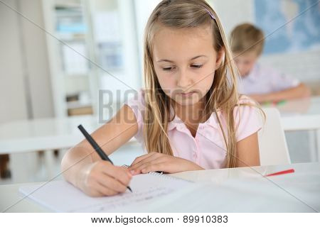 Cute schoolgirl writing on notebook, in classroom