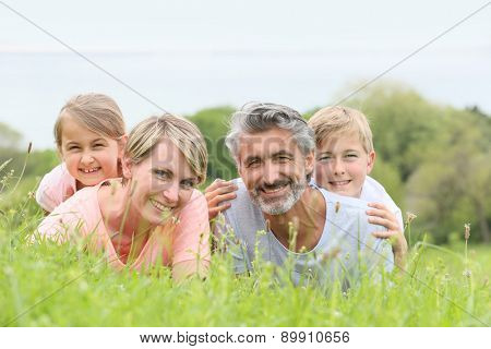Portrait of family laying down in grass