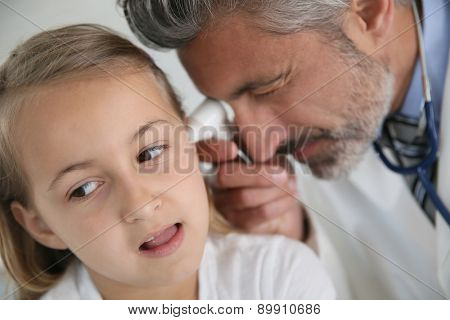 Doctor examining girl's ear
