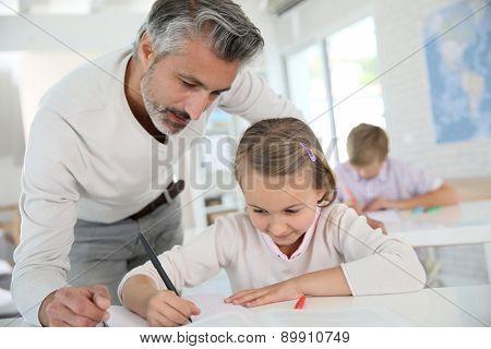 Teacher with schoolgirl in class