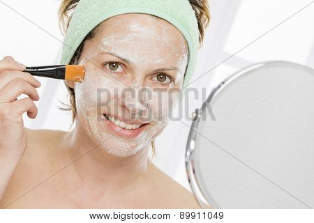 Forty years woman putting mask on her face