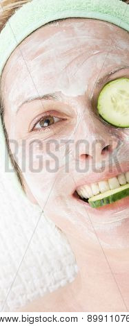 Forty years woman with face mask and cucumber