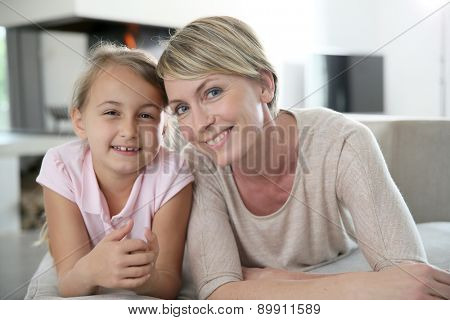 Portrait of mother and daughter laying in couch at home