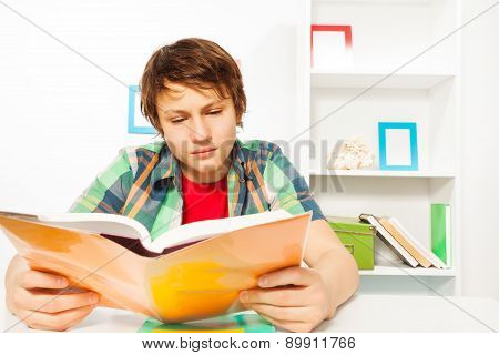 Clever boy read book sitting by table do homework