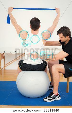 Man on yoga ball working with a physical therapist against fitness interface