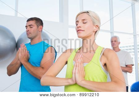 Fit people meditating with hands joined in gym class