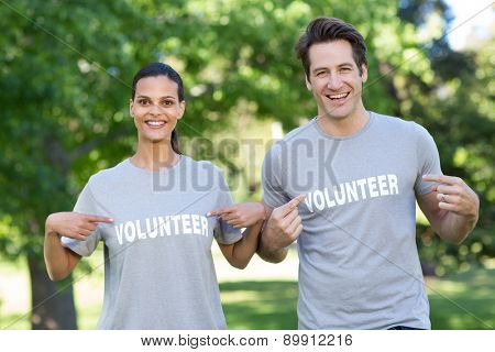 Happy volunteer couple smiling at the camera on a sunny day