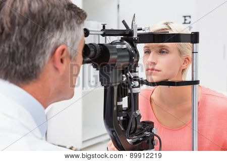 Optometrist examining blonde woman in medical office