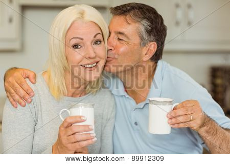 Mature couple having coffee together at home in the kitchen