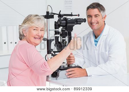 Portrait of senior patient gesturing thumbs up while sitting with optician in clinic